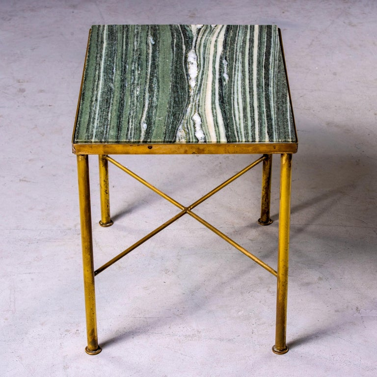 Found in England, this circa 1960s side table has a slender brass frame with X-form stretcher and green marble table top. Unknown maker.