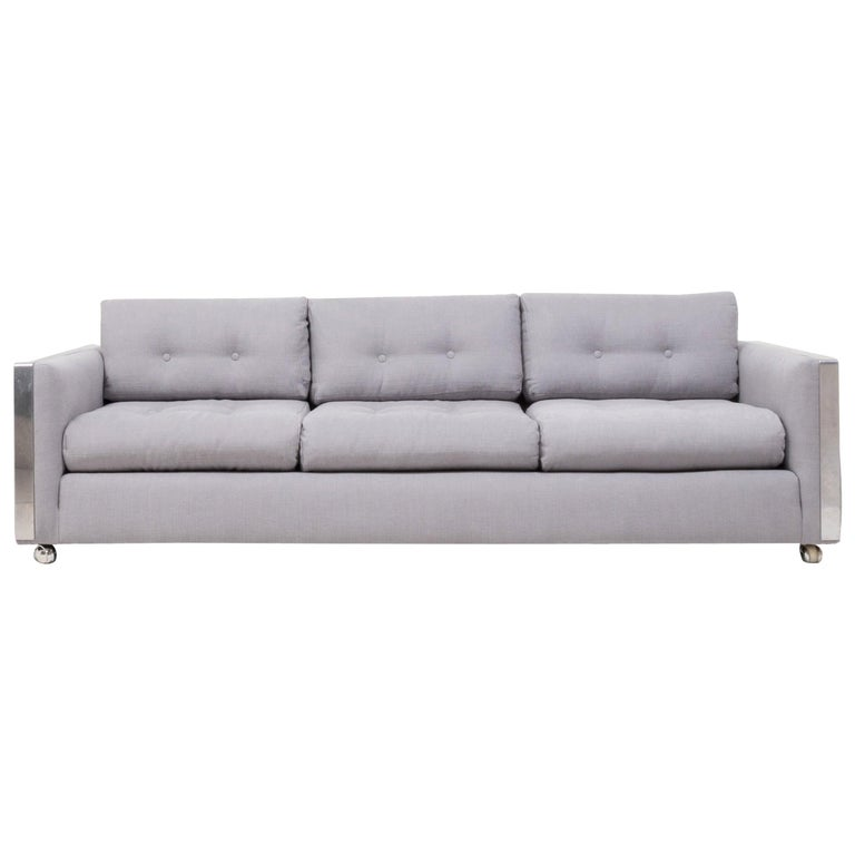 Designed in the style of Milo Baughman, this sleek three-seat sofa has been newly upholstered in a sumptuously soft and airy grey Linara fabric that compliments the chrome detailing perfectly.   With its clean lines and cool aesthetic it combines