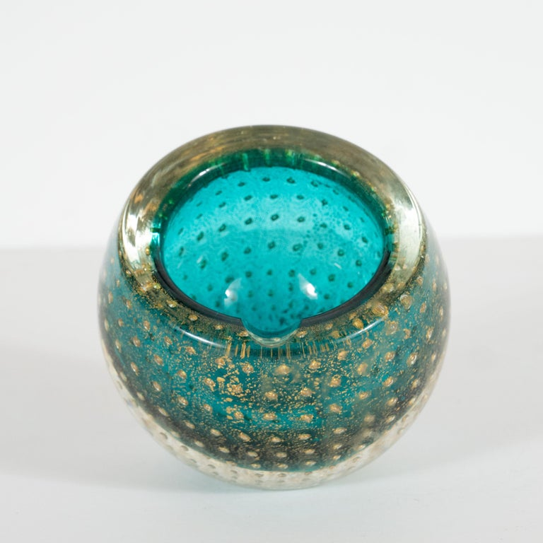 This elegant decorative bowl or ashtray was handblown in Murano, Italy- the island off the coast of Venice renowned for its superlative glass production, circa 1960. It features a spherical body with a circular mouth cut a bias with a translucent
