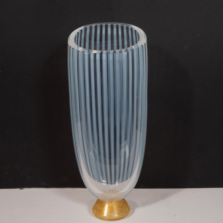 This stunning Mid-Century Modern vase was realized by Seguso- one of the most renowned glass ateliers of the period- in Murano, Italy, circa 1960. It features an hourglass form with a conical base replete with an abundance of 24-karat gold yellow