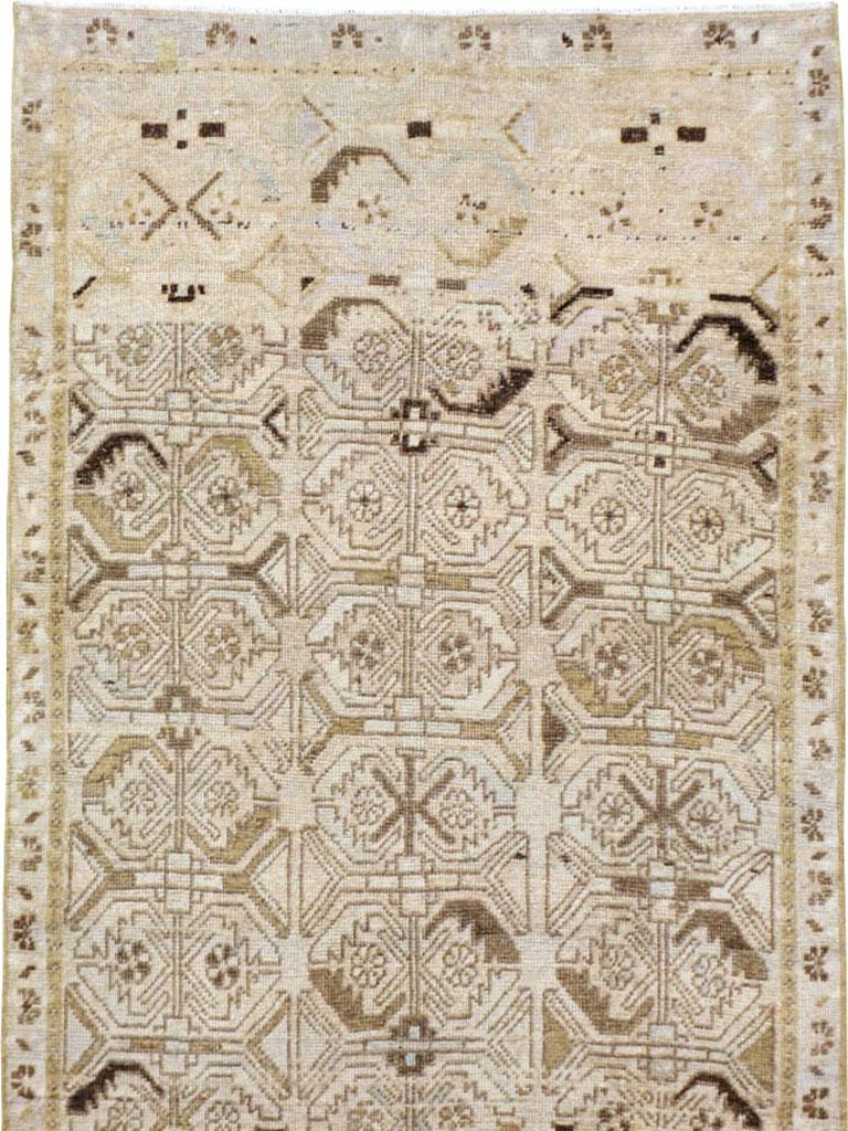 A vintage Persian Tabriz rug in runner format handmade in the mid-20th century with a beige field, and minor secondary tones in light purple and light blue.  Measures: 3' 6
