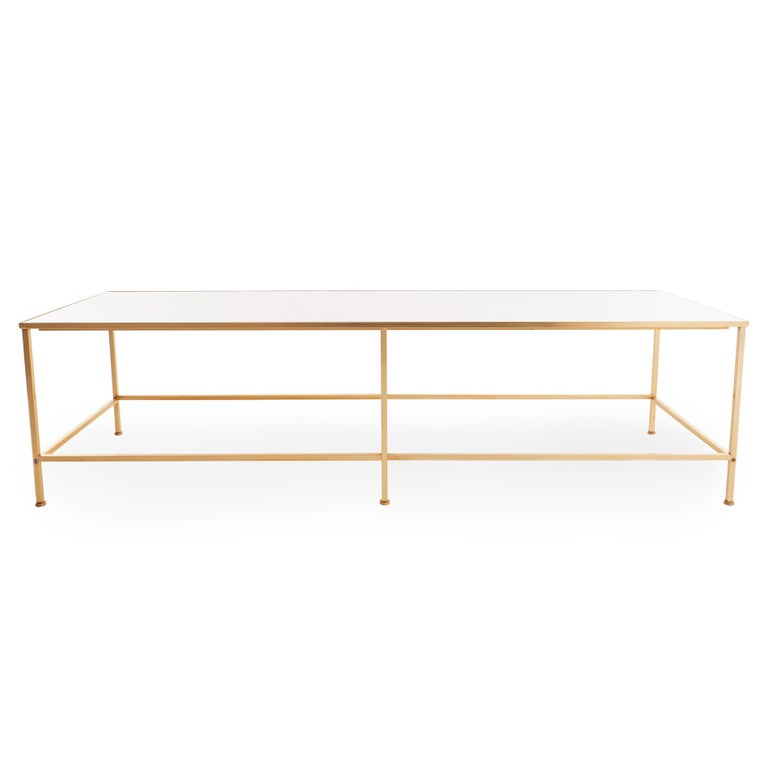Sleek midcentury coffee table with substantial white vitrolite top inset into a brass frame, in the style of Harvey Probber. Overall in incredible shape, with a small hairline crack in one corner (see images).  Measures: 16