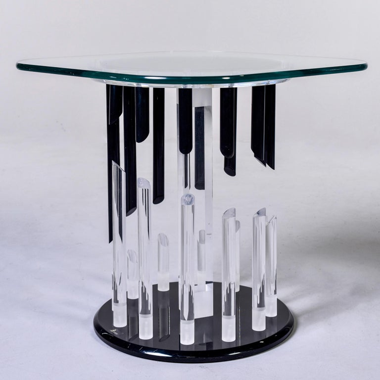 Side table with a Lucite base by Haziza, circa 1980s. Table has a black Lucite base with clear and black Lucite rods with diagonally cut ends that form an abstract pattern. Top of base is clear Lucite and tabletop is a glass square with rounded