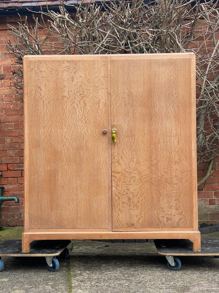 Magnificent early 20th century heal's attributed limed oak two-door wardrobe compactum, England, circa 1930.  The rectangular top with canted corners over two figured, panelled solid oak doors with carved knob handles opening to reveal brass