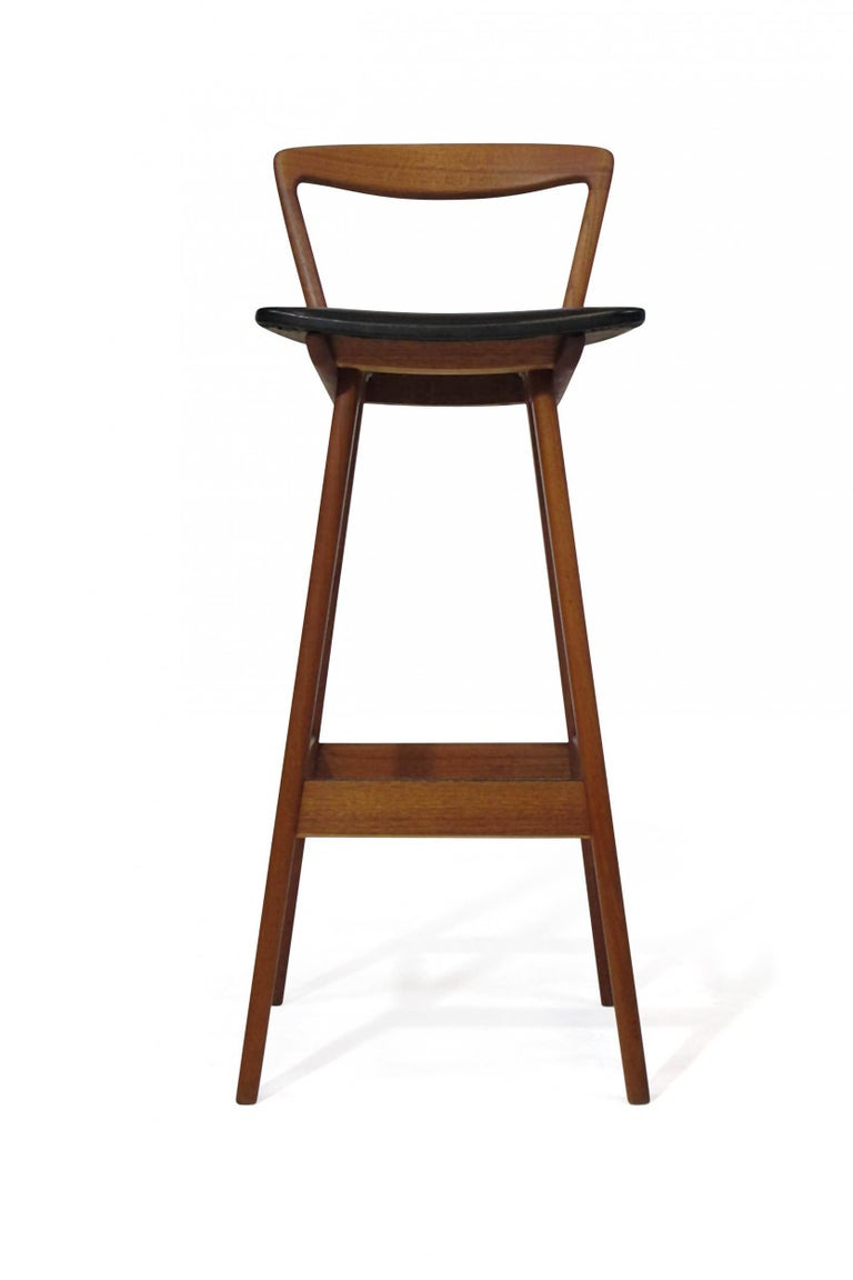 Midcentury teak bar stools designed by Henry Rosengren Hansen for Brande Mobelfabrik model 43, Denmark. Barstool crafted of solid teak frames, elegantly sculpted backrest with the original black vinyl seat raised on flared legs. Excellent condition