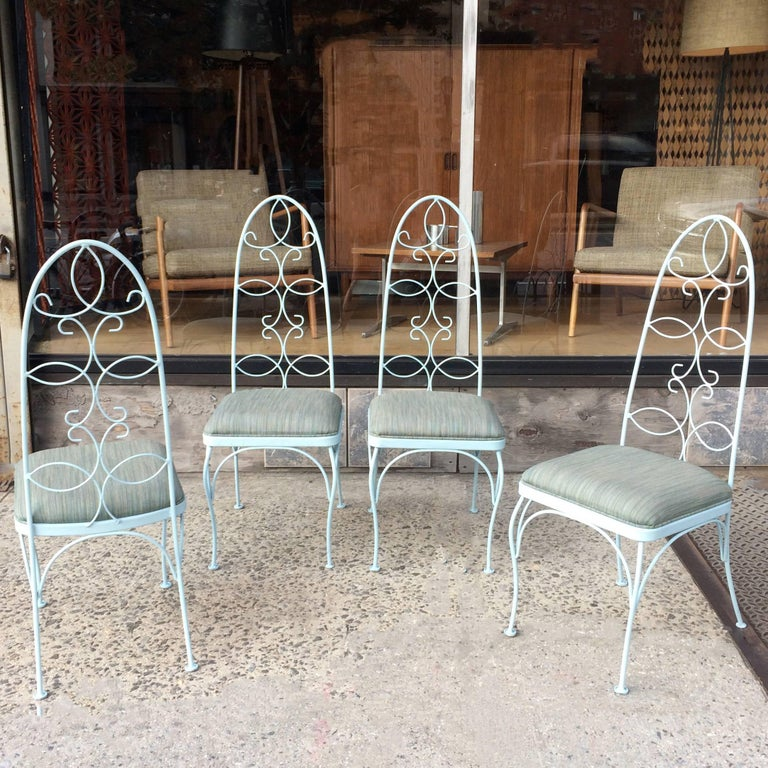 Set of four, mid century, patio, garden, outdoor chairs feature scrolled, wrought iron, high back frames newly painted in light blue and newly upholstered seats in durable outdoor fabric.