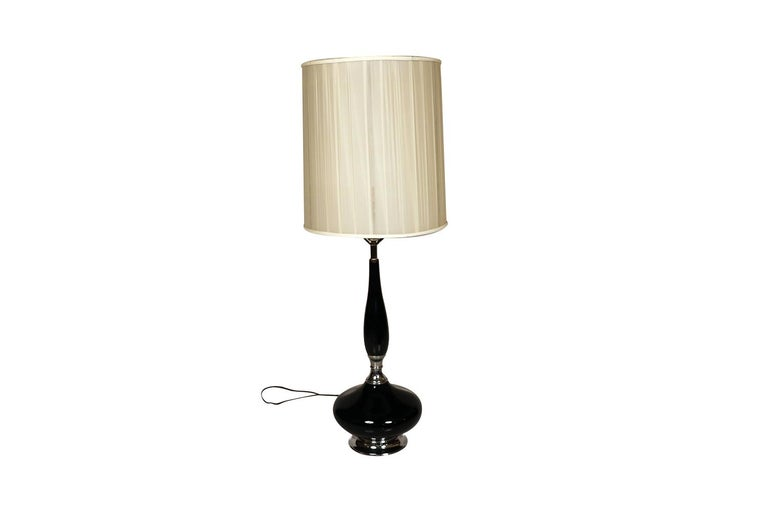 This is a stunning and very sought after midcentury, Hollywood Regency, ceramic table lamp with an elongated neck, over bulbous form, raised on a chrome base, finished off with this beautiful drum lampshade included, featuring a vibrant shiny black