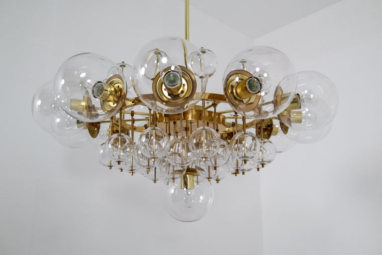 Large midcentury hotel chandelier with brass fixture, large hand blowed glass globes and smaller hand blowedglass globes. The pleasant light it spreads is very atmospheric. Completed with the clear glass and brass details, this large chandelier will