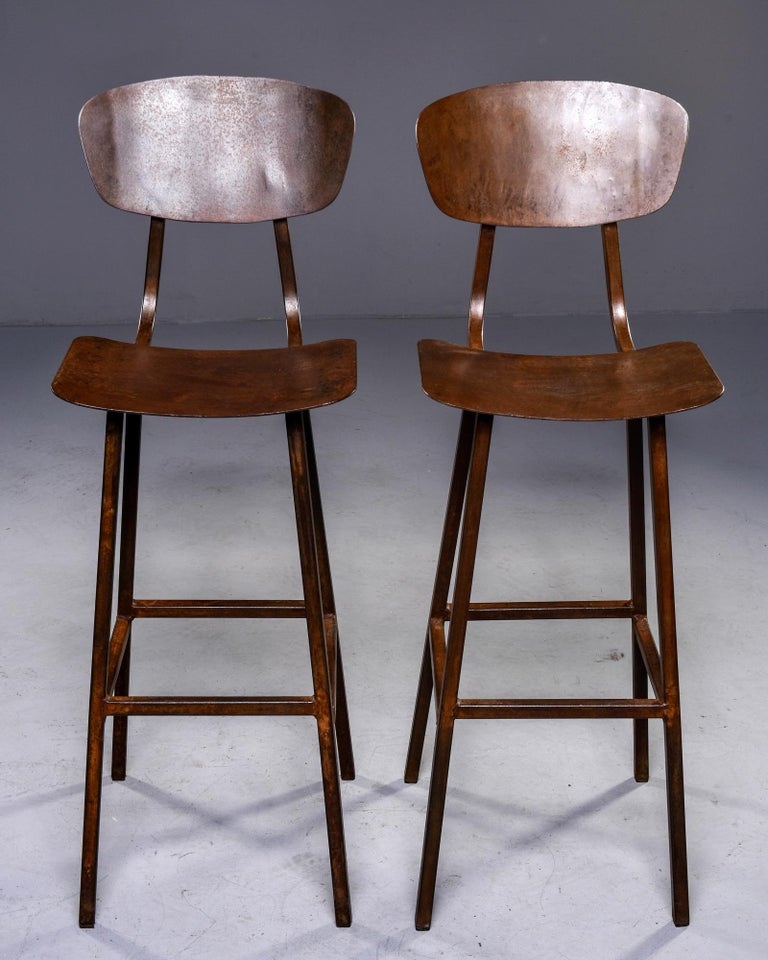 """Sold individually, these circa 1940s bar height industrial stools were found in England and are made of welded iron and have a rusty brown colored finish.   Measures: Seat height: 28.75 to 29"""", seat depth: 11"""", seat width: 14.75""""."""
