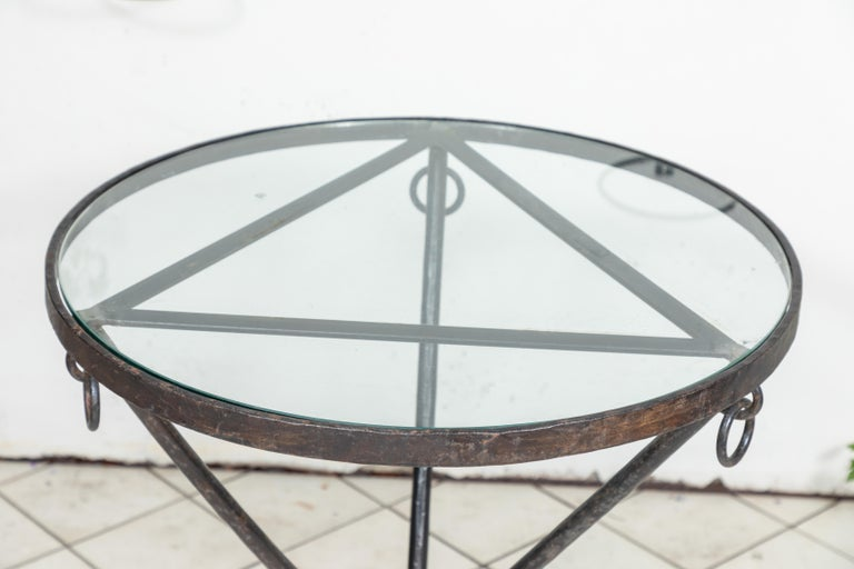 Midcentury iron and glass round table with ring details, circa 1950.