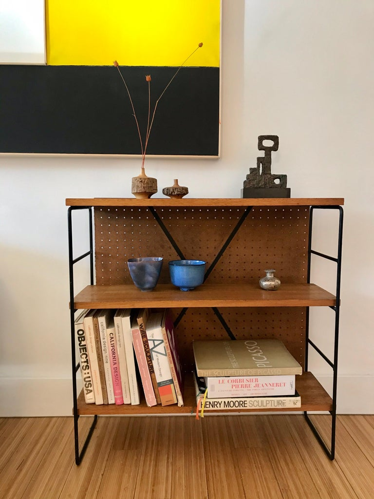 A nice architectural design. Made of powder-coated steel with solid mahogany wood shelves and Masonite backboard. Great for any space Display pottery, books and art objects.