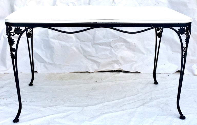 1950'S Wrought Iron black floral and vine motif rectangular dining table. Features a daisy motif on curved legs. White laminate top, slightly warped.
