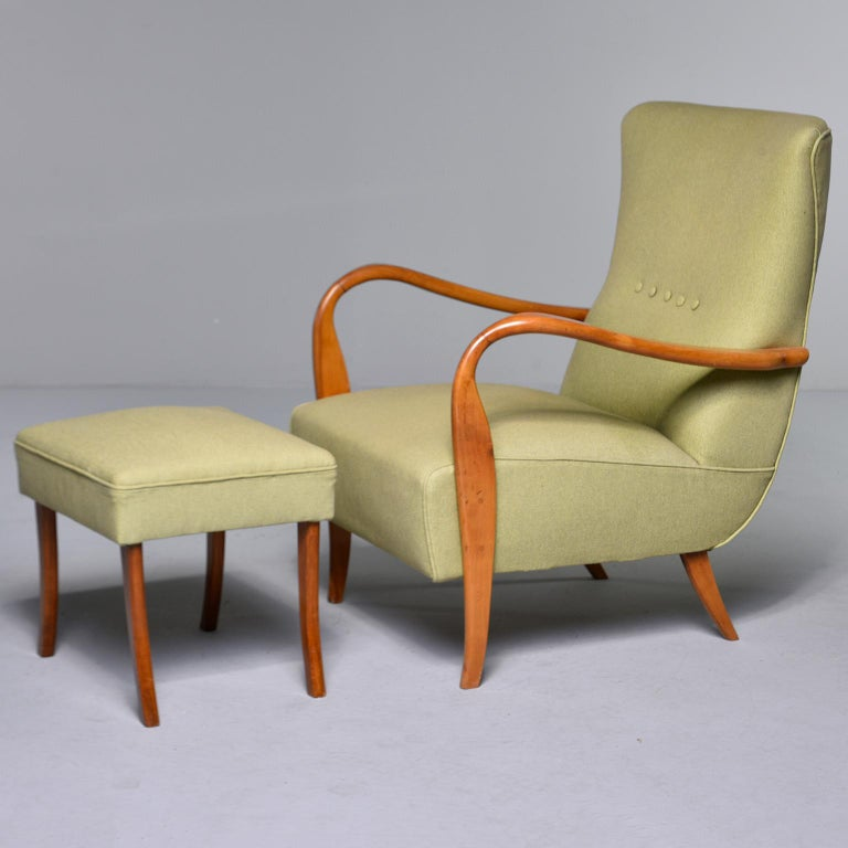 Italian upholstered armchair and stool, circa 1950s. Chairs feature dramatic, curvy polished wood arms, matching footstools with saber legs, tall backs with button embellishments and new upholstery in celery green linen-blend fabric. Unknown maker.