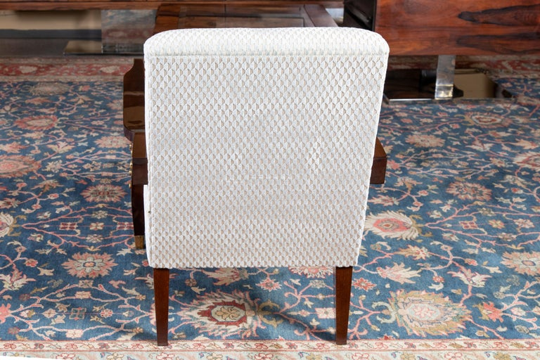 Chairs are newly re-upholstered in a light colored fabric. Their wooden arm supporters are gradually transferring into the 2 front legs, which have bras tips at the end. There are 6 brass decorative round elements on the outer side of each arm rest.