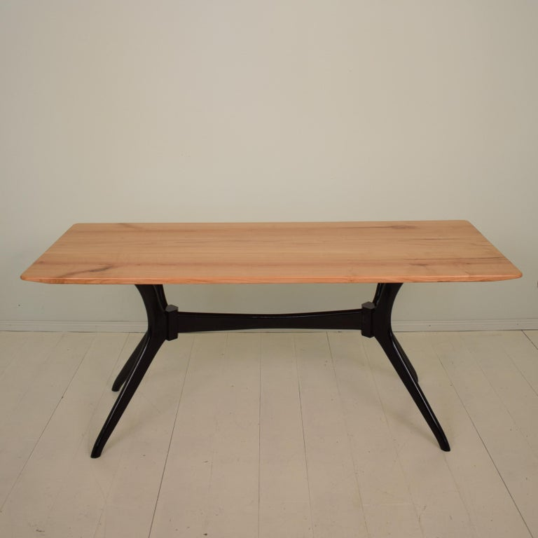 This elegant midcentury Italian dining table is made in the style of Ico Parisi. The sculptural base is ebonized beech and the tabletop is made out of solid cherrywood. (the top is replaced). A unique piece which is a great eyecatcher for your