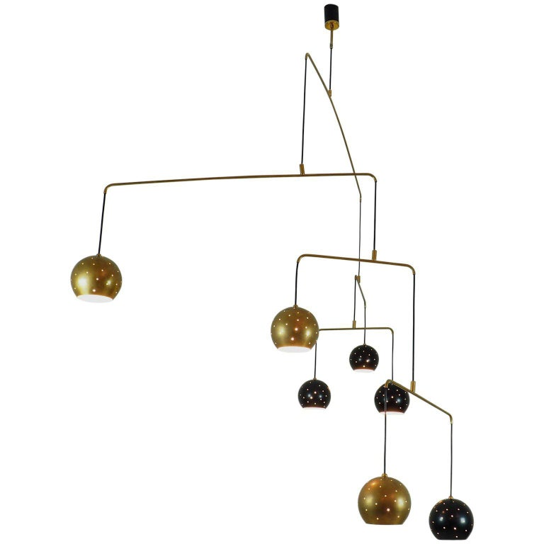 Original Italian brass mobile chandelier manufactured in a very small handcraft production in Milano, 20th century Large, magic and poetical mobile chandelier with brass and black suspending spheres, it can moves with the flow of air. Wholly in