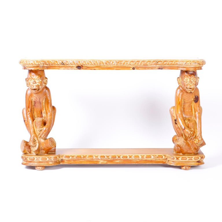 Whimsical carved pine console table with a desirable slim profile, scalloped top, carved monkey supports and a stylized base with bun feet.