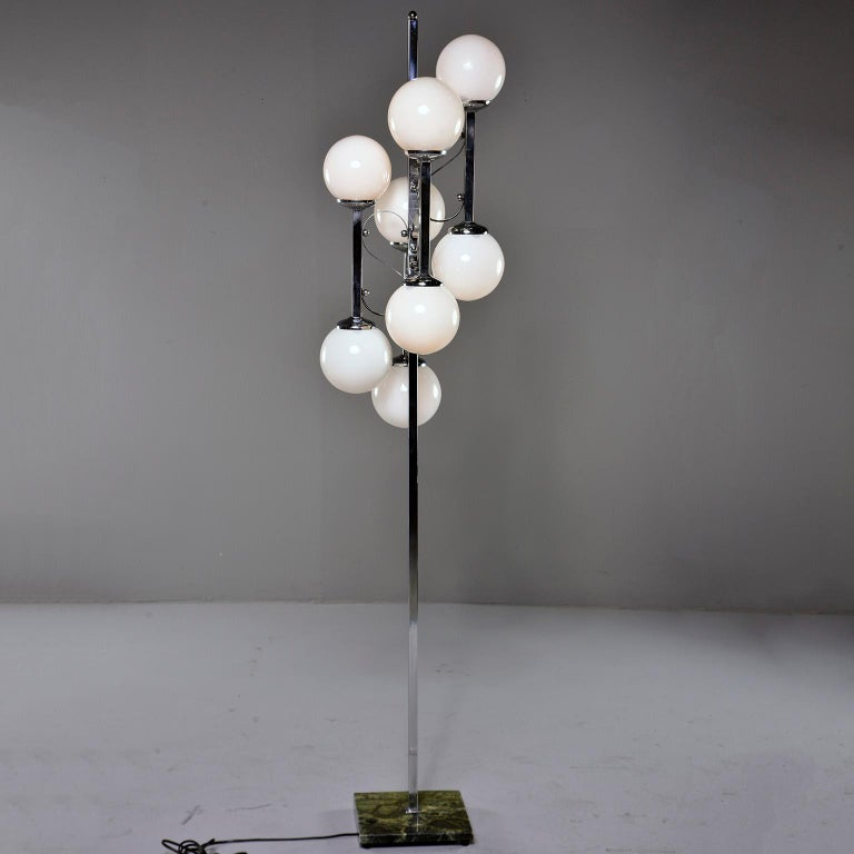 Italian floor lamp has a green marble base with polished chrome center support with four arms and eight white glass globes with candelabra sized sockets, circa 1970s. Unknown maker. New wiring for US electrical standards.