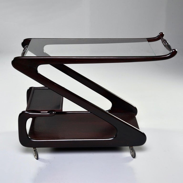 Italian bar cart or drinks trolley has a dark stained wood frame in the shape of a modified Z circa 1960s. Top has glass shelf and handle. Bottom has solid shelf with another smaller shelf that forms a second tier. Unknown maker. Very good vintage