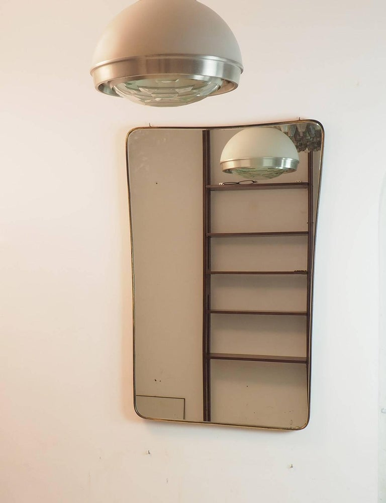 Italian extra large wall mirror, measures: 120 x 80 cm, 47.24 inches x 31.50, with curved brass frame and bevelled original mirror, 1950s. General good condition with original patina of the brass. High quality of the thick brass frame. Just a