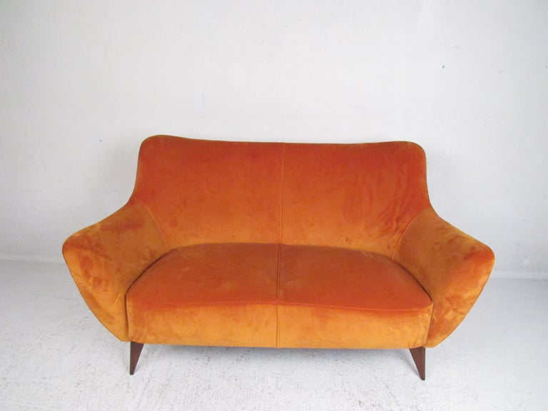 This elegant vintage modern sofa features splayed walnut legs, winged armrests, and a thick padded seat. The elegant orange velour upholstery makes this piece pop in any seating arrangement. In the style of Gio Ponti. Please confirm item location