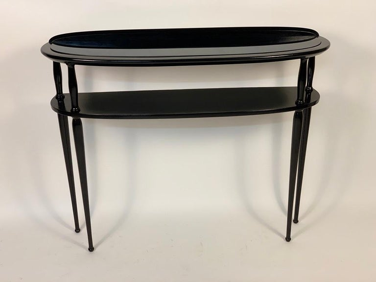 Half moon console, two shelves, the upper one with black glass embedded in the structure. Four tapered legs. Italy, 1950s.