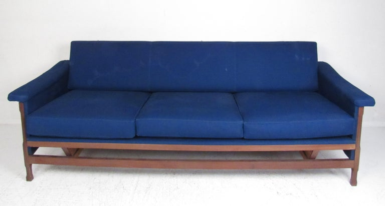 This stunning vintage modern set includes two lounge chairs and a three-seat sofa. A sculpted walnut frame, winged armrests, and royal blue upholstery add to the midcentury appeal. This sleek and comfortable living room set makes the perfect