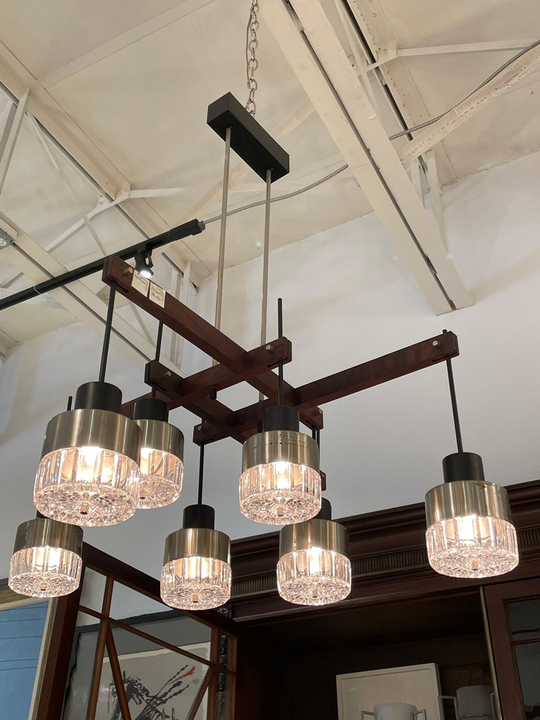 In the style of Stilnovo, this wonderful 8 light glass, walnut and metal chandelier with original canopy is extremely sculptural, geometric and modern for a classic mid-century light.