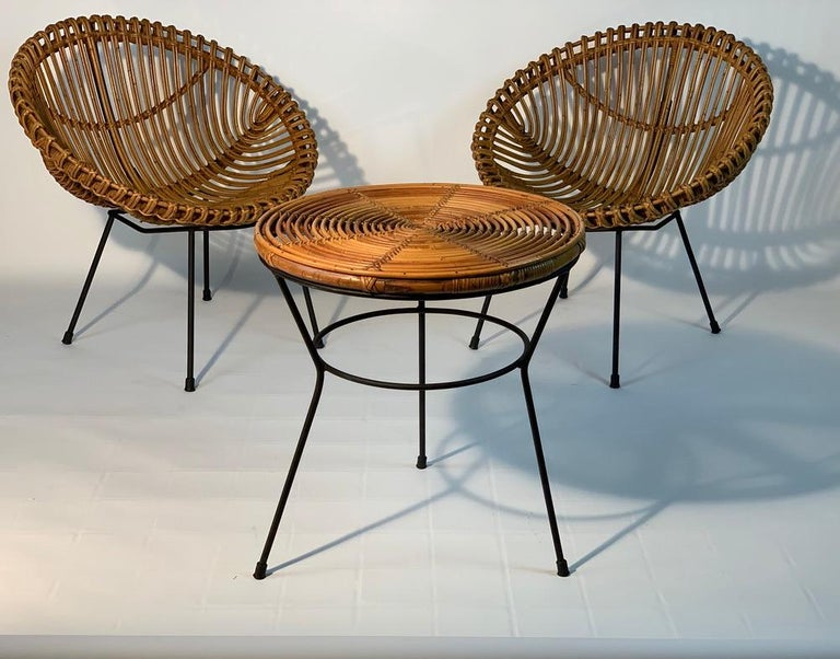 Set composed of two Italian midcentury armchairs in the shape of a nest and a round bamboo rattan coffee table or side table with legs in black lacquered metal. Italy 1950s. The listed measures are about the armchairs . The measures table height