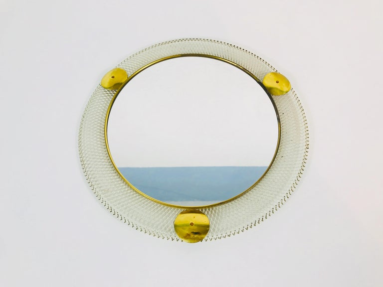 A round wall mirror from the 1960s made in Italy. The mirror has a circular metal design. The mirror is in a good vintage condition.