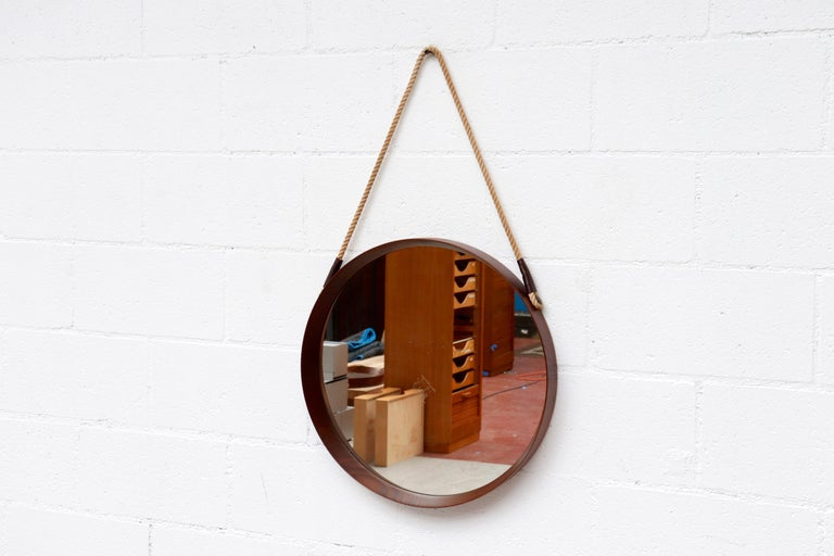 Mid-Century Round Jacques Adnet Style Teak Hanging Mirror with Brass Pegs and Rope Strap with Leather Detail. In Original Condition with Minimal Wear Consistent with Age and Use. Mirror has some reflective mirror loss, see photos Strap lengths may