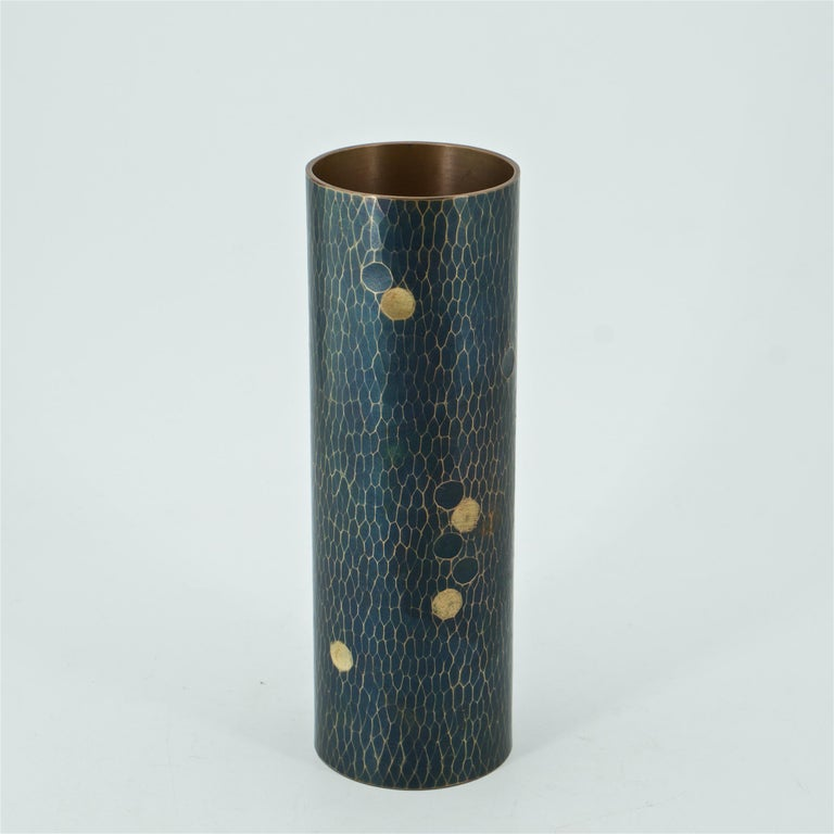 A fine vintage Japanese bronze and brass cylinder vase with a martele finish. Black patinated surface, polished ridges, and brass inlaid dots. Impressed maker's mark on verso.