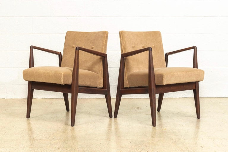 This pair of vintage Mid-Century Modern lounge chairs designed by Jens Risom are circa 1960. The iconic Classic Danish modern-inspired design features clean, Minimalist lines and distinctive angles. This set features a beautiful sculptural solid