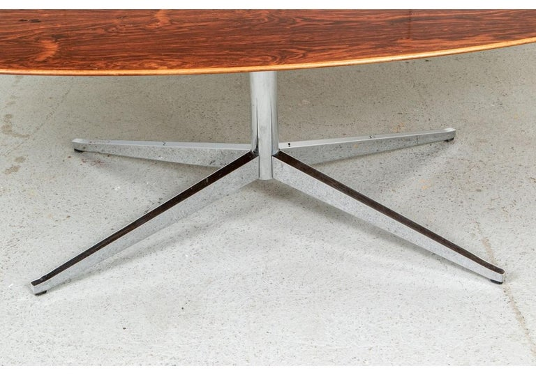 The Classic oval conference table dated 1976 in a larger size and in very good condition. Notably, the wood veneer is particularly rich, well grained and colorful. With a glass cover on the top. Mounted on a chrome four part base. Label underneath.