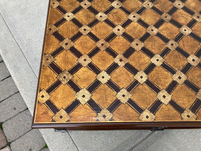 This large scale Mid-Century Modern coffee table has a stunning top with lacquered gilt and chocolate brown trellis decoration. The base is walnut with spiral legs over ball feet. The removable top is inset into the base showing the gilt sides. It