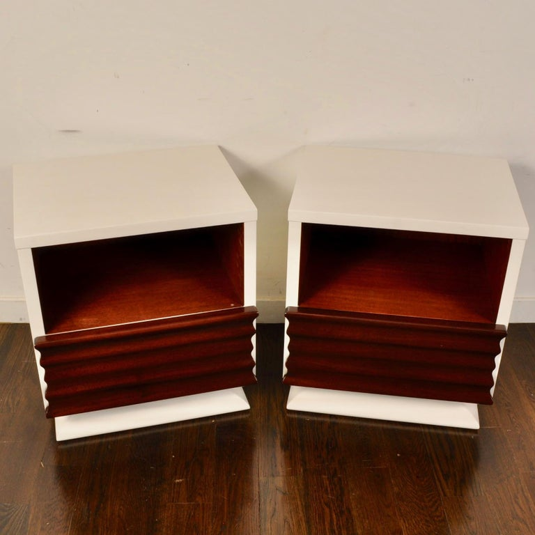 Nice sculptural front mahogany nightstands from the 1950s that have been updated with a white lacquer. Each piece features a deep cubby and a bottom drawer.