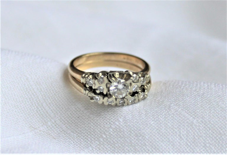This ladies 14 karat yellow and white gold and diamond matching engagement ring and wedding band set was made during the 1960's, most likely in the United States. The engagement ring features one brilliant cut and prong set diamond with a clarity
