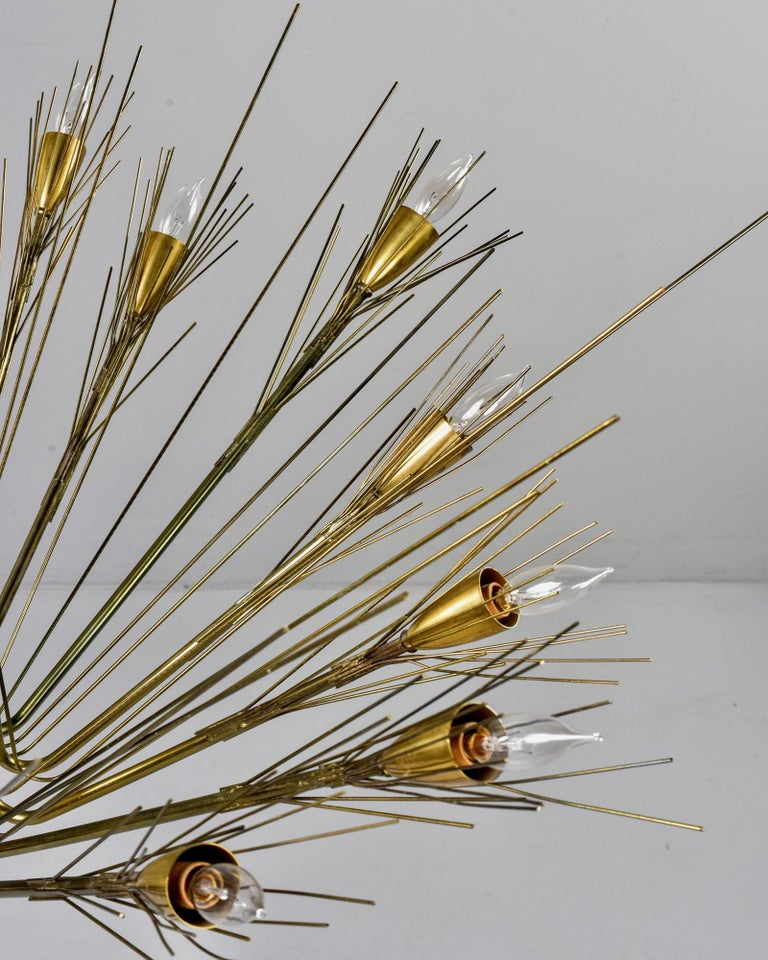 Large 14-light circa 1960s brass brutalist style chandelier. Thin brass rods form the frame of this chandelier. Unknown maker. Found in US. Candelabra sized sockets. New wiring and original polished brass canopy.  Rod only (from fixture to