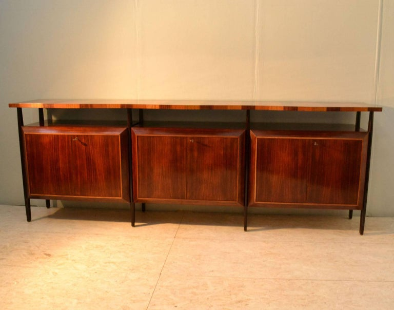 Unusual handcrafted sideboard with three units in palisander veneer with diamond shaped fronts doors, suspended on ebonised legs. An overlapping zig-zag edge top floats on top of the legs in borders of three colored wood; Indian palisander, blond