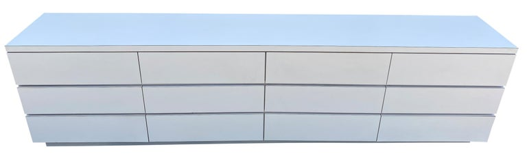 Very long matte white Formica laminate plywood custom 12-drawer dresser credenza, circa 1980s custom made to fit in a bedroom. Comes apart in 4 sections easy to move and assemble and set up as a floor dresser of mount on a wall as a floating