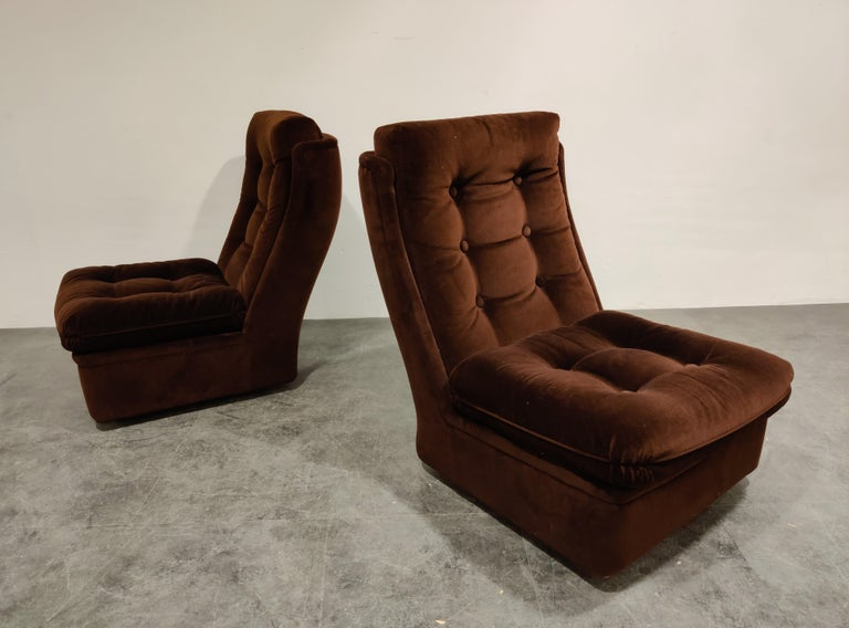 Pair of midcentury brown fabric lounge chairs on wheels.