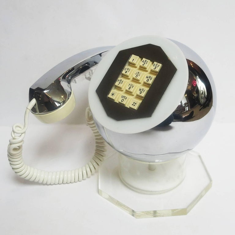 Create the ultimate statement with this wonderful Mod phone! The body of the telephone is a chrome ball, supported by a clear Lucite column and thick octagon base. The handset is a combination of chrome and plastic, and nests on a clear Lucite arm.