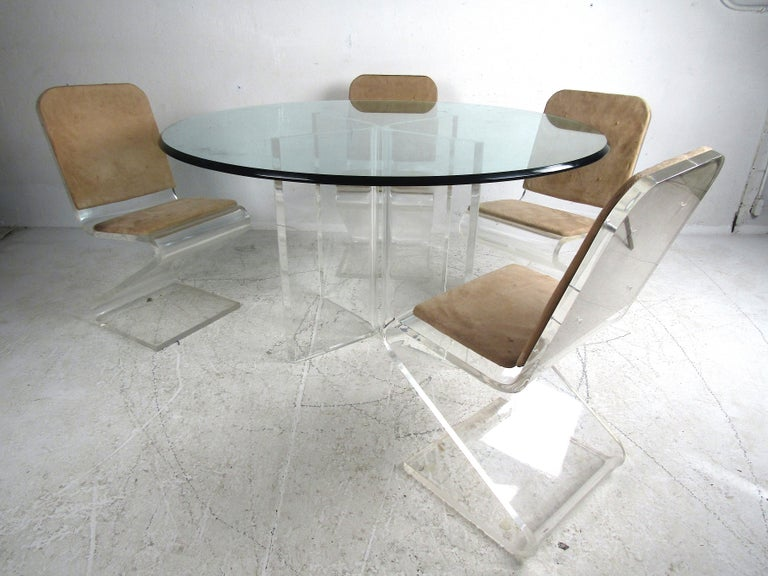 Stylish Mid-Century Modern Lucite and glass dining set. Large circular glass tabletop with adjustable Lucite bases. Set of 4 dining chairs with Lucite