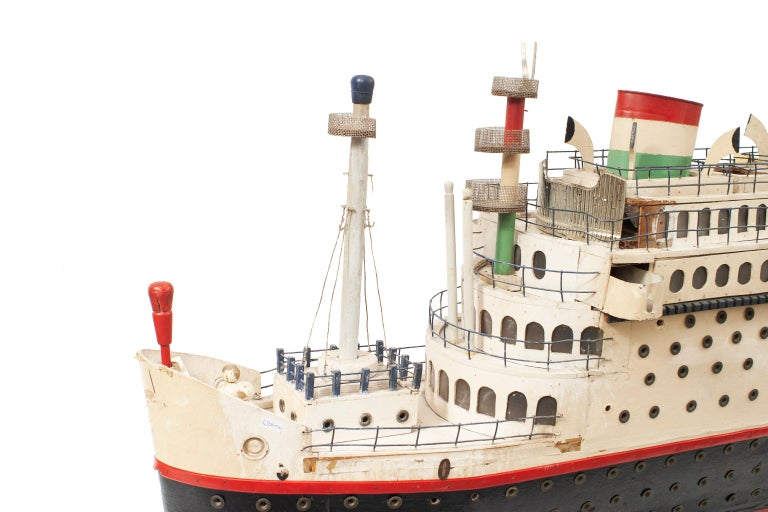 Mid-century model of a luxury liner boat / ship model painted red, white and blue with 2 smoke stacks supported on a stand.