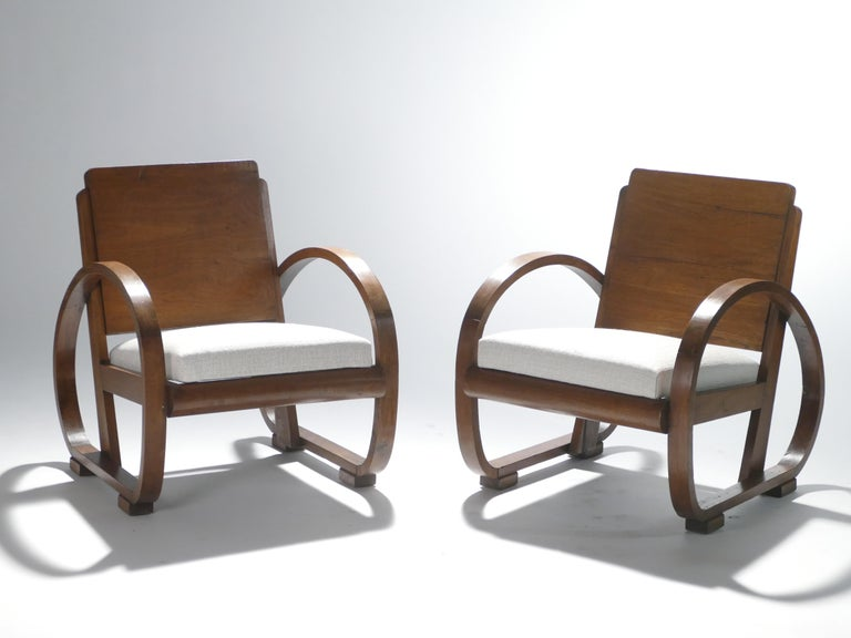 Lend your living room an unparalleled modern elegance with these 1940s armchairs. The arresting structure, rich creamy colors, and quality material make these pieces a stunning example of French art deco modernism. Lovely mahogany wood forms the