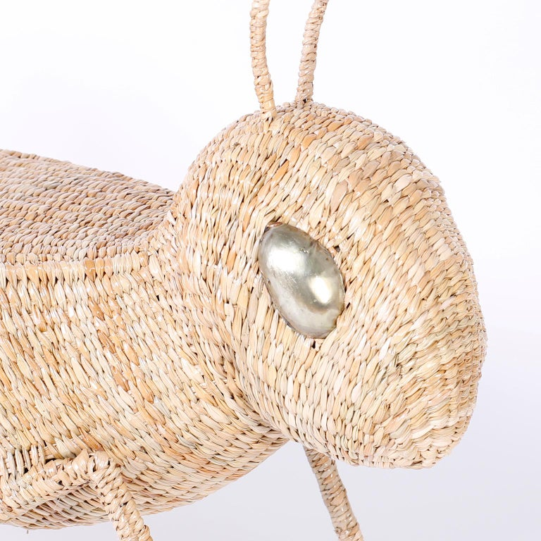 Unconventional folky cricket or grasshopper table crafted in wicker and ambitiously woven over a metal frame, complete with antennae and striking bug eyes. Can be used as a table or enjoyed as an object or sculpture. Signed Mario Torres on a brass