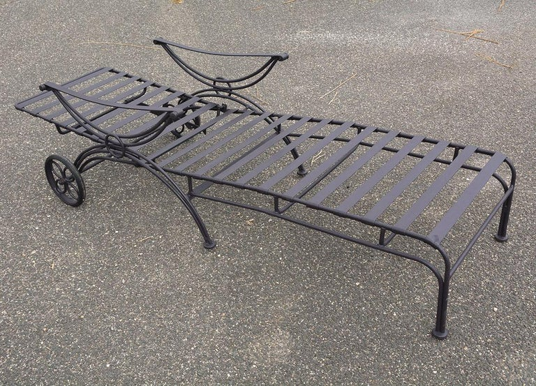 Reclining outdoor chaise lounge with painted black metal frame, flexible straps for added comfort on seat bottom and back. Two wheels on the chaise for easy movability.