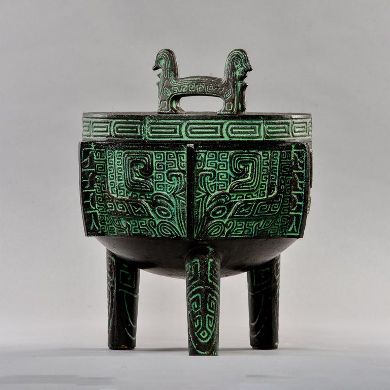 Circa late 1950s heavy cast metal lidded vessel / ice bucket with stainless steel liner features ancient chinese motifs and incised surface design. Often attributed to James Mont, this piece was produced by Getz Brothers & Co. Use as intended or