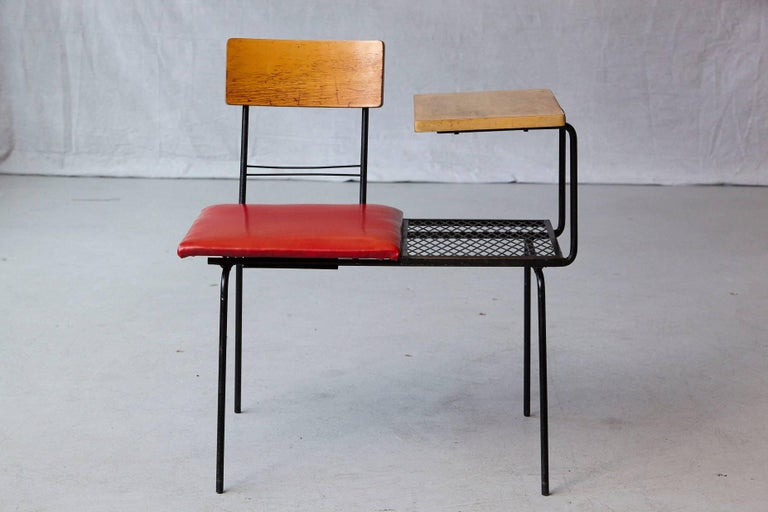Midcentury black metal wire telephone table with integrated bench or seat covered in red Naugahyde. The seat and back unit can be positioned in a 180 degree direction to fit for left or right hand people.