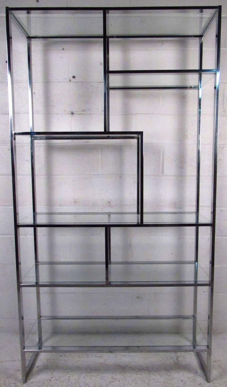 Vintage modern étagère featuring sculpted chrome body with glass inserts, designed by Milo Baughman. Ideal for any living room or store display this shelving unit adds a brilliant boost of sophistication to any space. While simplistic in design and